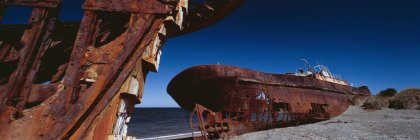 Panoramic view of abandoned shipwreck on shore at beach against dark blue sky — Stock Photo