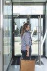 Portrait de femme heureuse portant un sac à provisions à l'entrée du magasin — Photo de stock