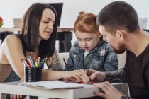 Parents drawing with daughter while sitting in living room at home — Stock Photo