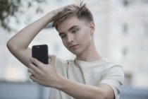 Ragazzo adolescente che prende selfie dal telefono cellulare con mano nei capelli — Foto stock