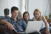 Smiling young friends using laptop while sitting on sofa at home — Stock Photo