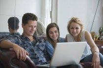 Усміхаючись молодих друзів за допомогою ноутбука, сидячи на дивані в домашніх умовах — стокове фото