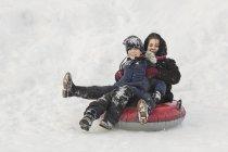 Портрет счастливой бабушки и внука, сидящих на надувном кольце в снегу — стоковое фото
