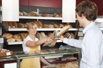 Sales clerk helping customer at bakery — Stock Photo