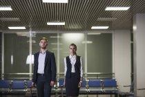 Ritratto di giovani uomo d'affari sicuro e donna di affari con bagagli in aeroporto — Foto stock