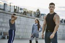 Ritratto di giovane atleta fiducioso in piedi con gli amici contro il ponte — Foto stock