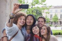 Lächelnde junge Frau beim Selfie mit multiethnischen Freunden, berlin, deutschland — Stockfoto
