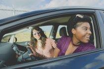 Sonriente a mujer joven mirando lejos sentado con amiga en coche - foto de stock