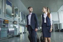 Young business people looking at each other while walking in airport — Stock Photo