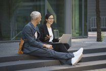 Smiling business colleagues with laptop discussing while sitting on steps in city — Stock Photo