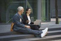Colegas de negócios sorridentes com laptop discutindo enquanto sentado em passos na cidade — Fotografia de Stock