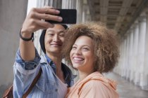 Smiling young man taking selfie with female friend in corridor — Stock Photo
