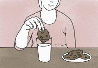 Мидсекция женщины, макающей печенье в молоко за столом на цветном фоне — стоковое фото