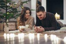 Sonriente pareja tomar café mientras se está acostado en la alfombra en su casa durante la Navidad - foto de stock