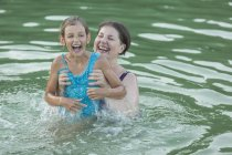 Smiling grandmother enjoying with granddaughter while swimming in lake — Stock Photo