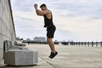 Young male athlete jumping on footpath against cloudy sky — Stock Photo