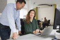 Щасливі бізнес колегами, обговорювати над ноутбук в офісному столі — стокове фото
