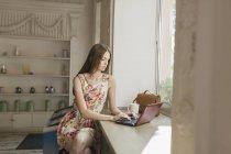 Mujer joven usando el ordenador portátil mientras está sentado junto a la ventana en la cafetería - foto de stock