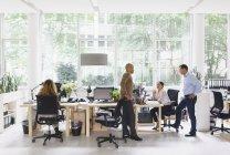 Empresaria que trabaja en el escritorio mientras sus colegas discuten durante la reunión - foto de stock