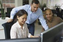 Lächelnde Geschäftsleute beim Anblick von Computern während eines Treffens im kreativen Büro — Stockfoto