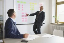 Happy businessman explaining to male colleague in creative office — Stock Photo