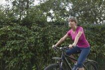 Femme à vélo avec haie sur fond — Photo de stock