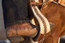 Crop cowboy boot in horse stirrup — Stock Photo