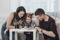 Parents drawing with daughter while resting in living room at home — Stock Photo