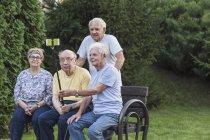 Sorridenti amici anziani scattare selfie con monopiede alla panchina del parco — Foto stock