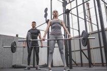 Athlètes masculins et féminins soulevant des haltères pendant l'entraînement Crossfit — Photo de stock