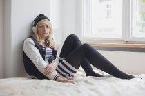 Портрет женщины, слушающей музыку через наушники, сидящей дома на кровати — стоковое фото