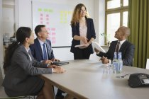 Businesswoman giving presentation to colleagues during meeting at conference table — Stock Photo