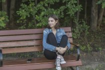 Улыбается молодой женщины, сидя на деревянной скамейке против деревья в парке — стоковое фото