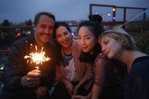 Ritratto di uomo felice che tiene scintillante mentre si siede con le amiche di notte — Foto stock