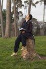 Mulher olhando para cima enquanto sentado no toco da árvore com livro — Fotografia de Stock