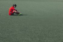 Вид сбоку сидящего на игровом поле футболиста — стоковое фото