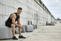 Portrait of confident male athlete sitting on seat at footpath — Stock Photo