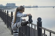 Female athlete stretching at railing on footpath — Stock Photo