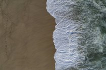 Drone view of wave on shore at beach, Porto, Portugal — стоковое фото