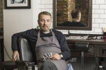Портрет зрілих Барбер, сидячи на стільці в перукарні — стокове фото