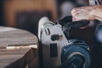 Geschnittenes Bild eines Schreiners mit Schleifer auf Holz — Stockfoto