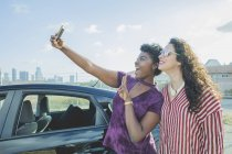 Happy young woman taking selfie with female friend at car against sky, Los Angeles, California, USA — Stock Photo
