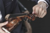 Cropped image of musician tuning violin strings — Stock Photo