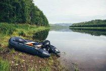 Надувний моторний човен, ошвартовані біля берега річки ліс — стокове фото