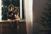Happy couple playing with sparklers while sitting on window sill during Christmas — Stock Photo