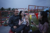 Happy couple talking to female friend holding wine on patio — Foto stock