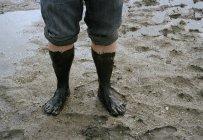 Crop male muddy feet on wet beach — Stock Photo
