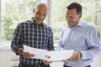 Smiling businessmen discussing over file against window in creative office — Stock Photo