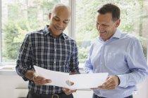 Sorrindo de empresários discutindo sobre arquivo contra a janela no escritório criativo — Fotografia de Stock