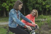 Mãe e filha falando ao mesmo tempo, andar de bicicleta no parque a sorrir — Fotografia de Stock